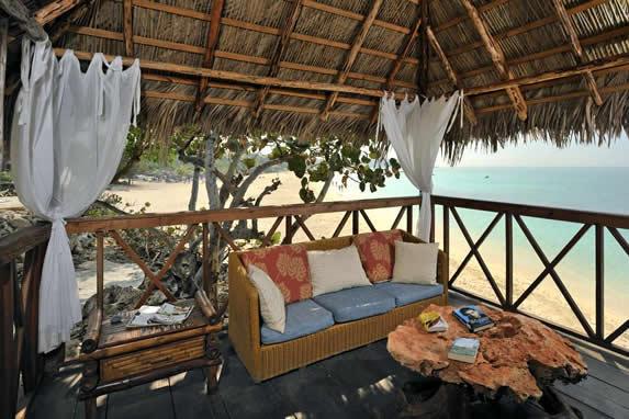 sofá de madera bajo techo de guano frente al mar