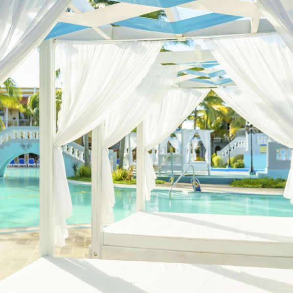 pool with sun loungers under white awnings