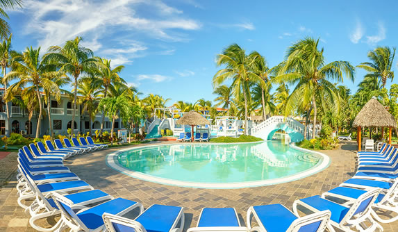 Pool surrounded by palm trees and blue sunbeds