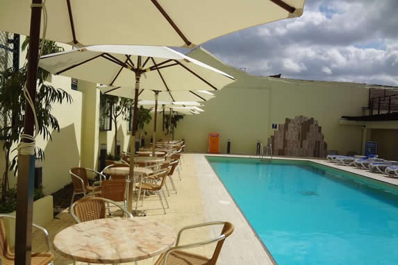 pool surrounded by sun loungers and umbrellas