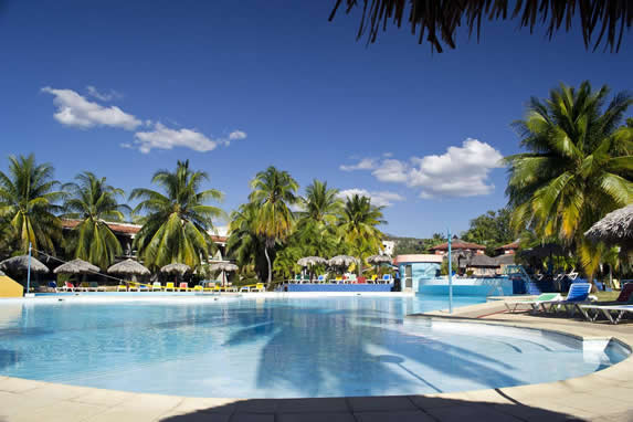 Hotel pool surrounded by palms and sun loungers
