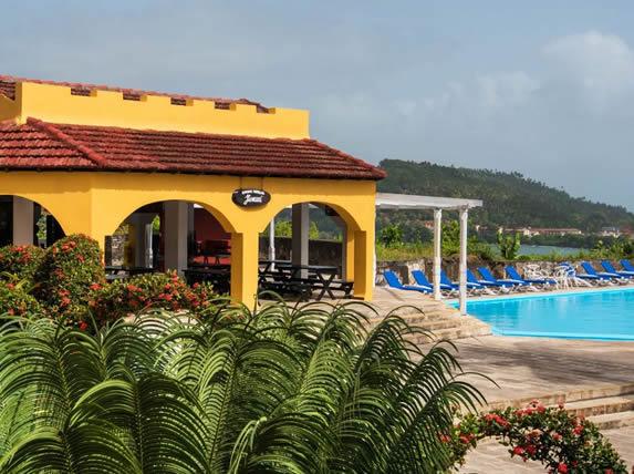piscina rodeada de tumbonas y vegetación