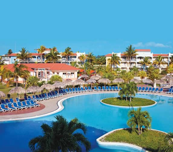piscina rodeada de tumbonas azules y palmeras