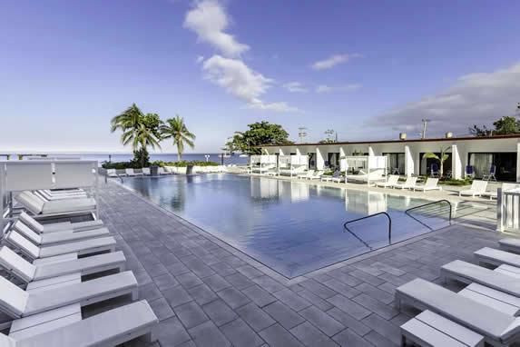 piscina con tumbonas y vista al mar