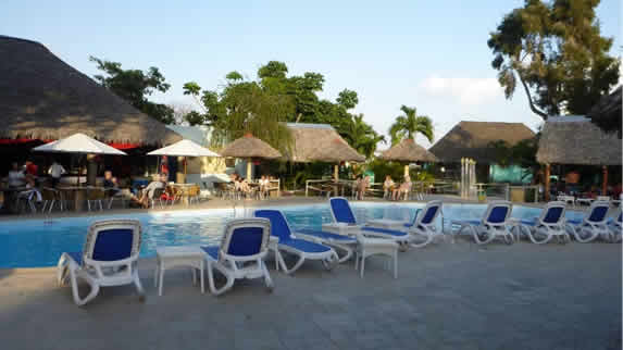 pool surrounded by blue sunbeds and umbrellas