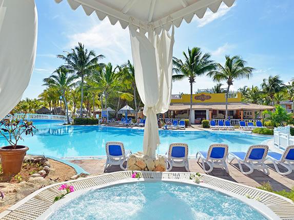 piscina rodeada de tumbonas y palmeras y jacuzzi