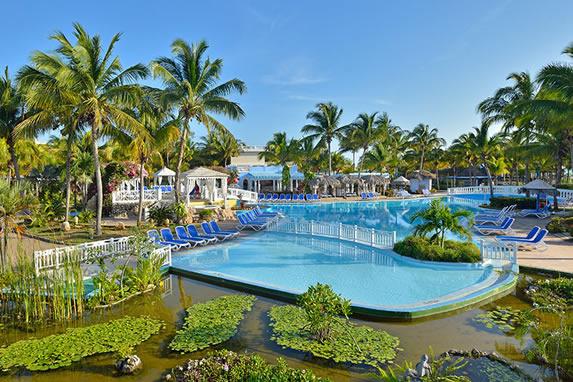 piscina junto a la laguna rodeada de palmeras