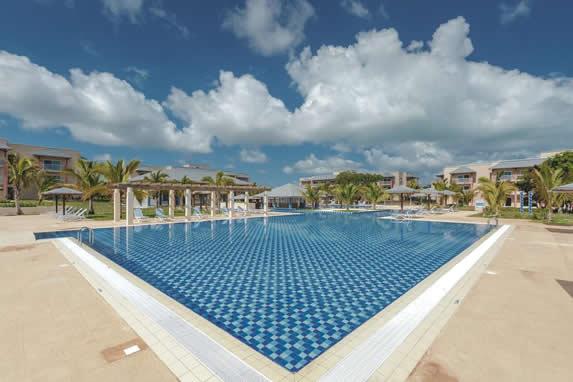 piscina con tumbonas y sombrillas alrededor