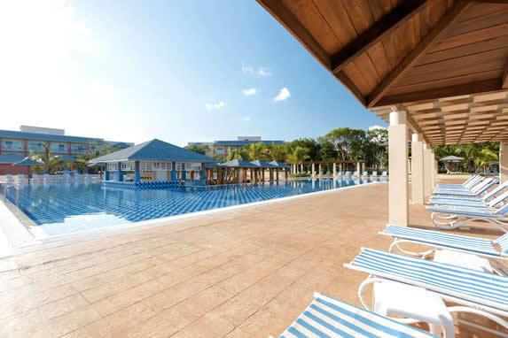 piscina con tumbonas y palmeras alrededor