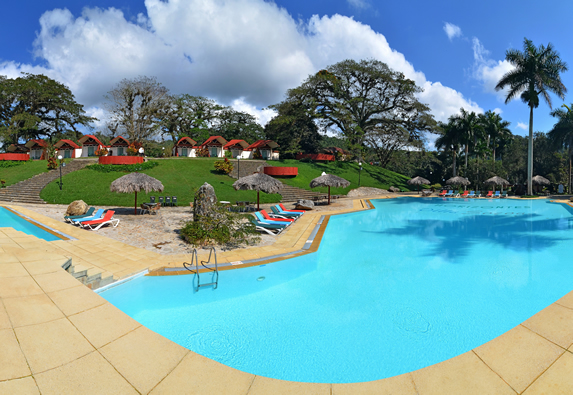 pool surrounded by sun loungers and guano umbrella