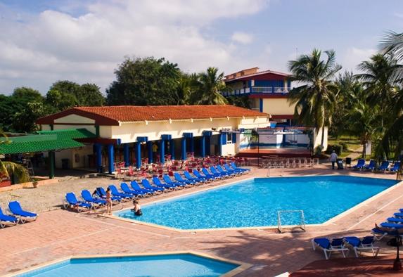 piscina rodeada de tumbonas y palmeras