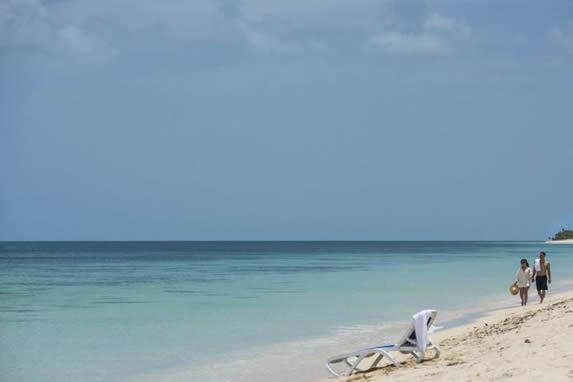 turistas caminando por la playa en un día soleado