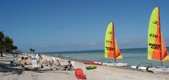 beach with sun loungers and sailboats in the sand