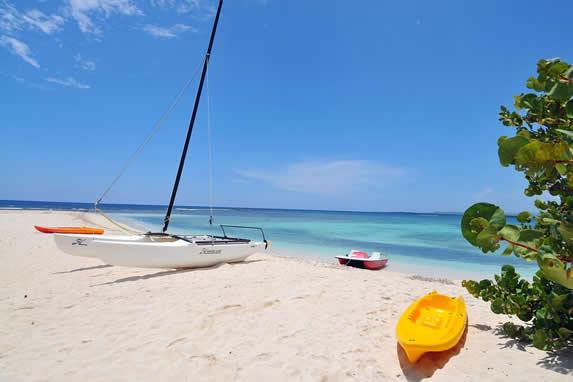 playa con catamarán y kayak en la arena dorada