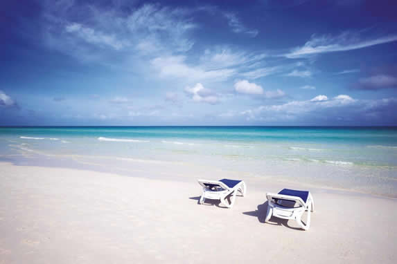 deserted beach with blue loungers on the sand
