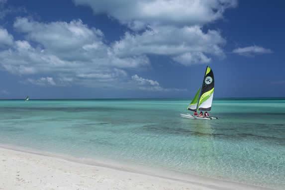 playa de aguas azules y catamarán navegando