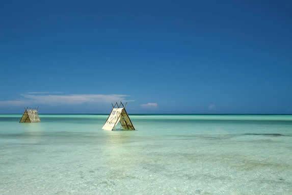 playa con techos de tela y madera en el agua