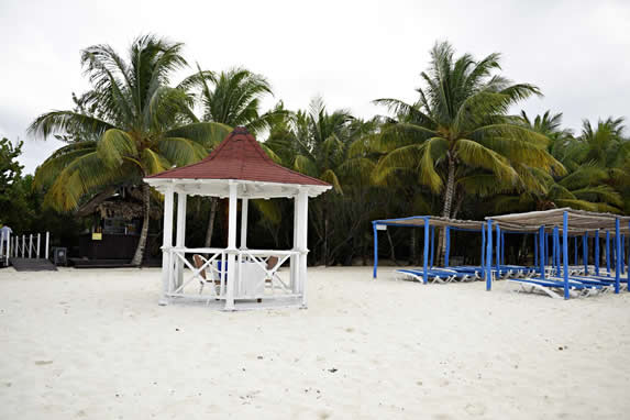 beach with loungers under rustic wooden roofs