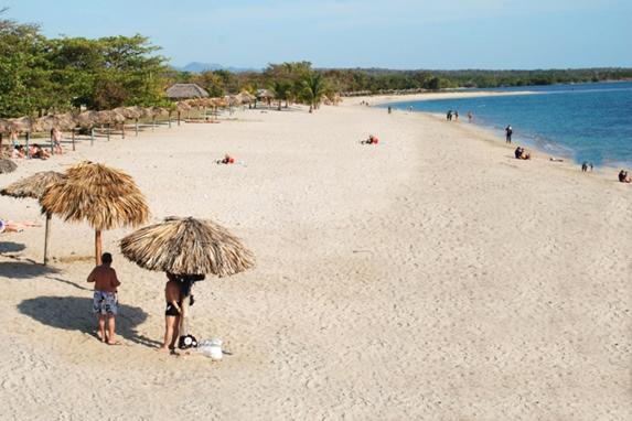 tourists on the beach under guano umbrellas