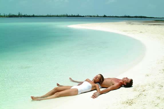 turistas tomando el sol en la playa