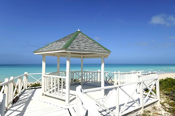 beach with white gazebo and blue sea