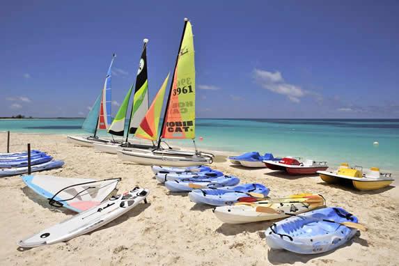 conjunto de veleros y kayaks en la arena