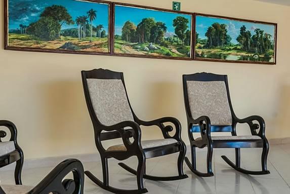 sillones de madera rodeados de cuadros decorativos