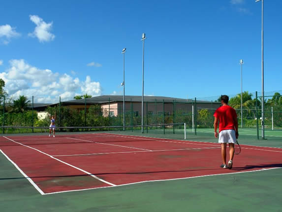 tourists playing tennis on the courts
