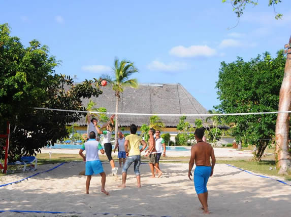 tourists playing volleyball on the sand