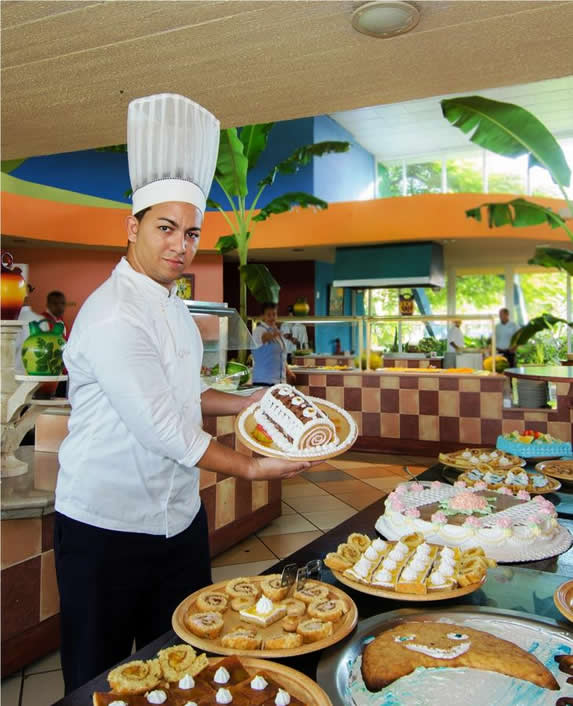 chef showing desserts from the buffet table