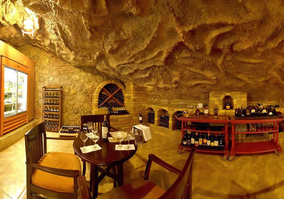cava con mobiliario de madera y techo de roca