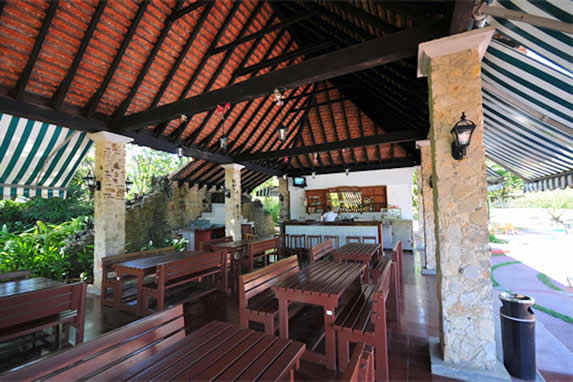 open restaurant with tile roof and furniture