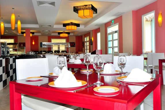 restaurante con mesas rojas y sillas blancas