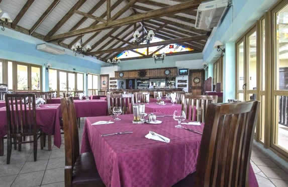 restaurant with wooden bar and tablecloths