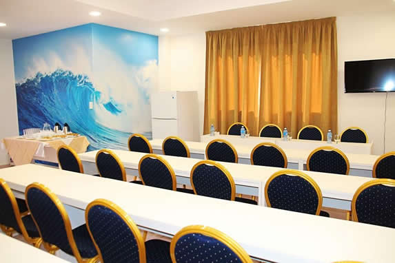 lounge with meeting tables curtains and TV