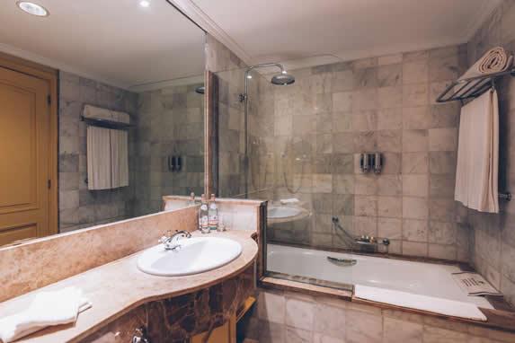 baño con jacuzzi y lavamanos de mármol