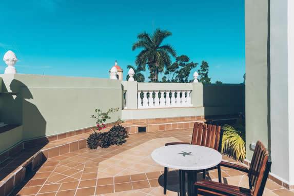 terraza de edificio colonial con sillas y plantas