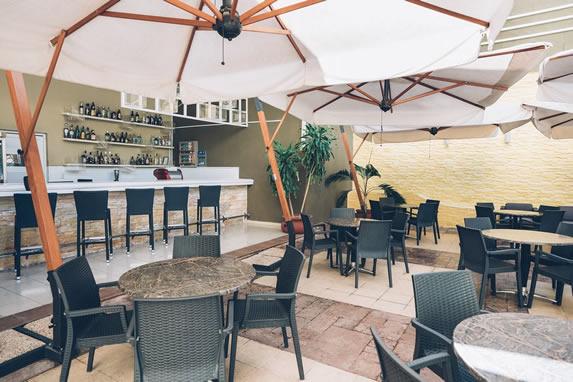 terraza con barra y mesas bajo sombrillas blancas